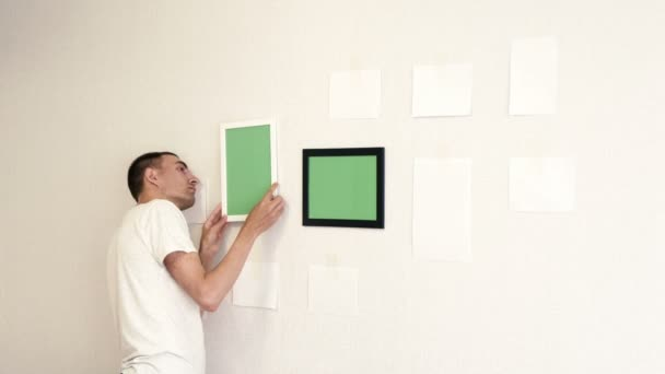 Young man hangs a white photo frame on a wall. Man corrects photo frames by building level.