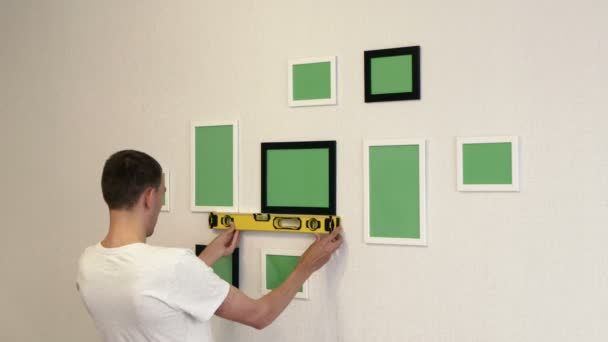 Young man corrects photo frames by building level. Photo frames hang on a wall.