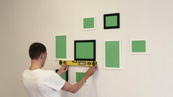 Giovane uomo corregge cornici dal livello di costruzione. Cornici fotografiche appese a una parete.