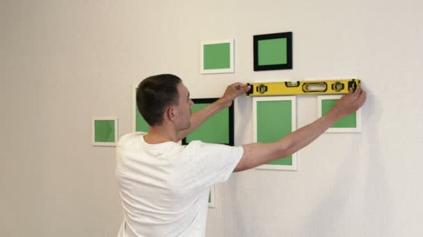 Young man corrects photo frames by building level. White and black photo frames hang on a wall.