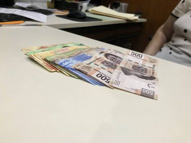 Many mixed Mexican peso bills spread over a beige desk