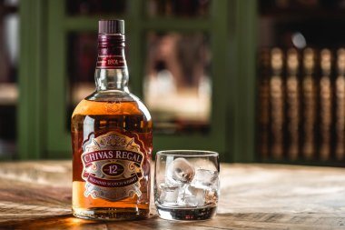 Chivas Regal whiskey bottle and glass with ice cubes on wooden table in dark bar. Chivas Regal is famous brand of Scotch aged popular whiskey