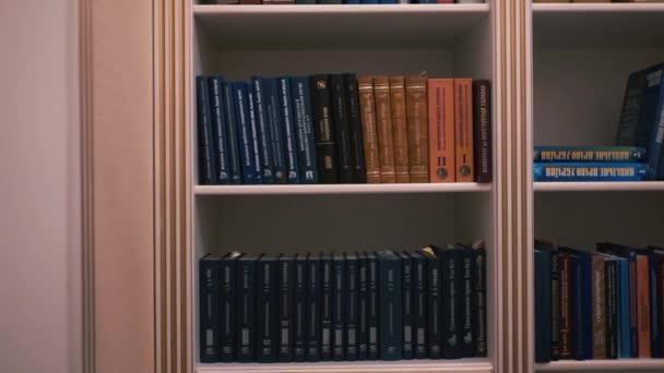 Könyvespolc a hazai könyvtárban. Sok könyv a polcról