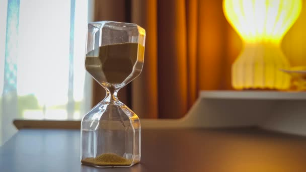 Sand running through the bulbs of an hourglass. Hourglass as time passing concept for business deadline