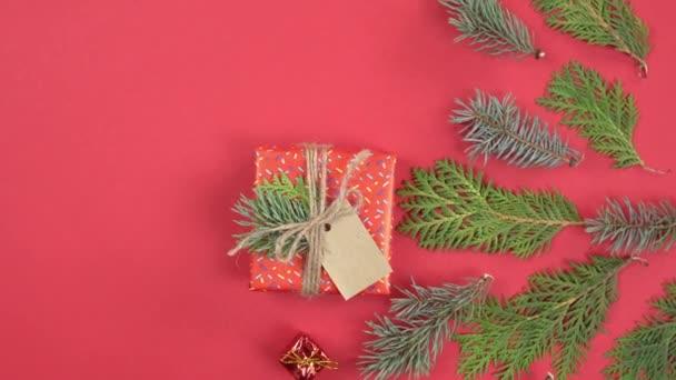 Vánoční pozadí 360 stupňů rotace. Jedlové větve stromů a dárková krabice rotující na červeném pozadí. Koncept Nového roku dárky, slavnostní a sváteční nákupy