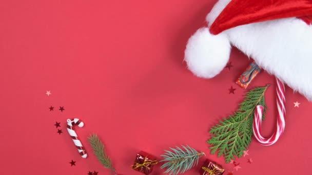 Vánoční pozadí 360 stupňů rotace. Santa Claus klobouk s dekorací a jedle větve točí na červeném pozadí. Koncept Nového roku dárky, slavnostní a sváteční nákupy