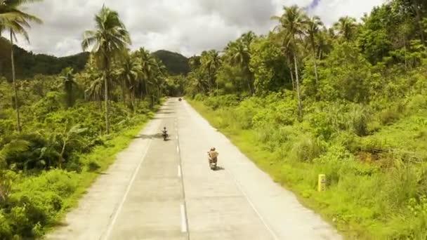 Fiatal pár túrák a dzsungelben egy robogó, utazás, szabadság, boldogság, nyaralás, nászút koncepció
