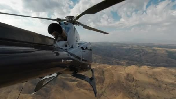 A US Army helicopter flies over the mountains in Afghanistan. View from the tail of the helicopter in 4K