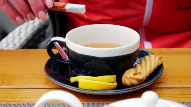 Az emberek és italok koncepció-nő kezében ömlött cukor a csésze teát kávézó