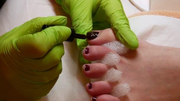 4k zaostřená lázně a koncepce krásy. Mistr pedikúra v zelených rukavicích aplikováním lak na nehty. Profesionální pedikúra
