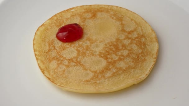 Close up. On a pancake draw a smiley face with strawberry syrup. Food concept.