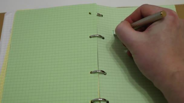 Aus nächster Nähe. Die Hand schreibt mit einem Füllfederhalter ins Tagebuch, einen Plan für den Tag, grünes Papier
