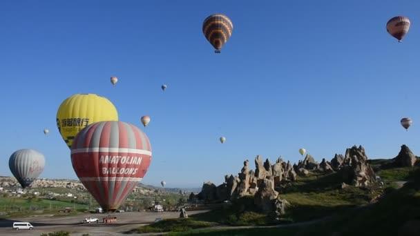 Panoramatický výhled na neobvyklou skalnatou krajinu v Cappadocia v Turecku. Barevné horkovzdušné balónky létají na obloze přes hluboké kaňony, údolí a pohádkové komíny Cappadociského kraje.