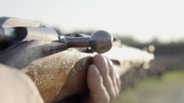 Egy ember lő egy öreg puskát. Közelről