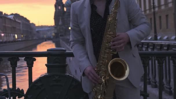 Szaxofonos egy könnyű öltönyt egy híd a beállítás nap, játszik a szaxofon.