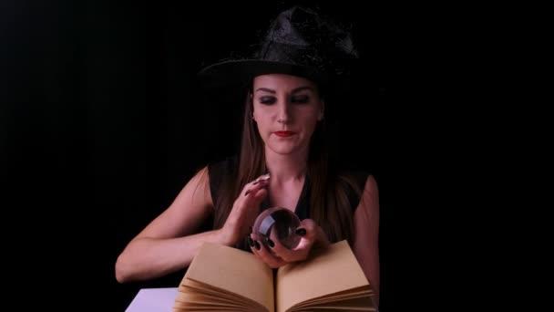 Atraktivní mystická čarodějka s jasně rudými rty na černém pozadí, dívá se do kouzelné koule při obsazení kouzel vedle knihy kouzel