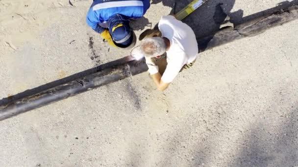 A védtelen munkások egy rozsdás fémcsövet hegesztenek. felülnézet, veszélyes munka koncepciója.