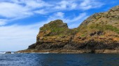 Photo Cape Brett in the Bay of Islands, New Zealand. The tip of the headland jutting out into the water