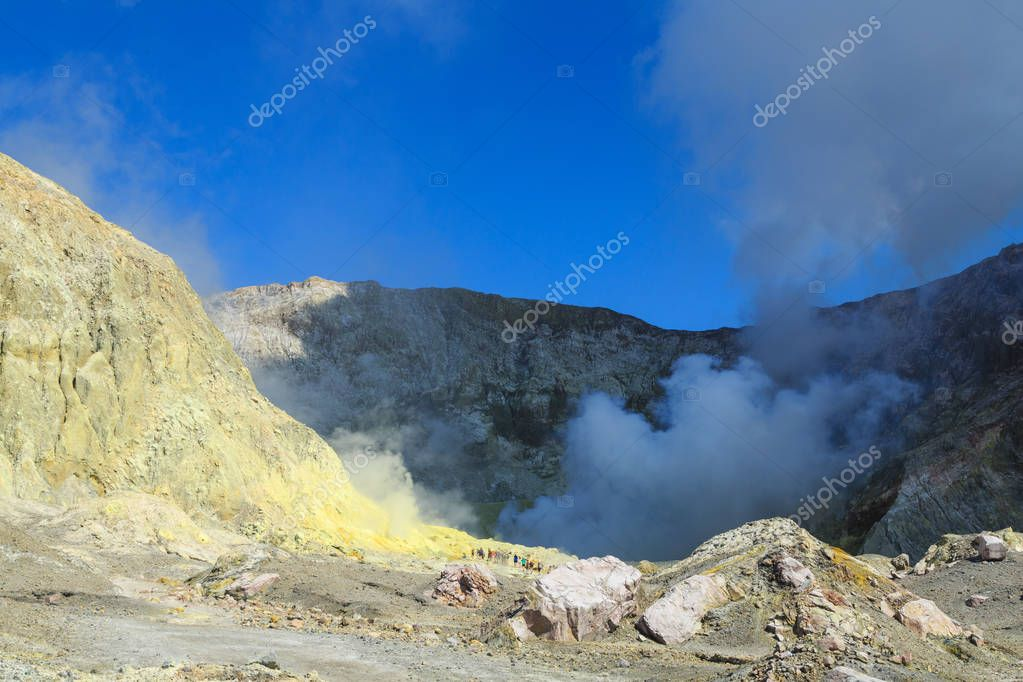 White Island, an active volcano in the Bay of Plenty, New Zealand. A party of tourists can just be seen trekking through the stark, sulfur-stained landscape to the steaming crater lake.