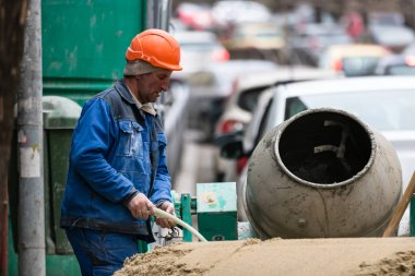Construction wokers on building site mixing cement in Bucharest, Romania, 2020