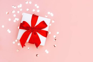 Gift box with red ribbon on pale pink background with golden confetti. Festive concept.