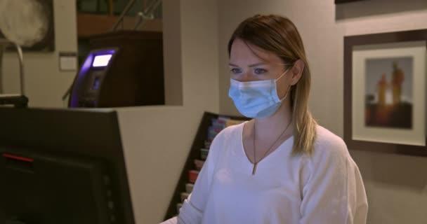 Müde Frau mit Gesichtsmaske arbeitet spätabends am Computer an der Rezeption