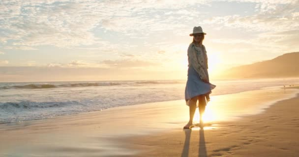 Cheerful beautiful woman is dancing on the beach in golden sunset light. USA
