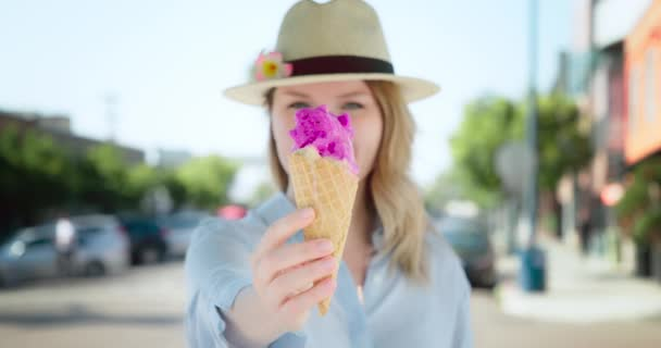 Bright pink ice cream in the waffle cone. 4K slow motion woman eating gelato