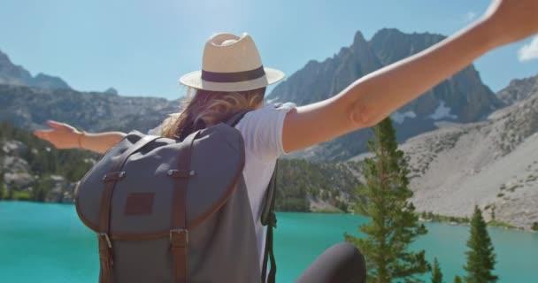 Žena těší přírodu a jezero s výhledem na hory. Zpět pohled cestovatel v přírodě