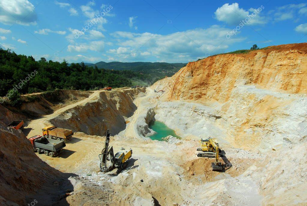 big machines and trucks work in a quarry