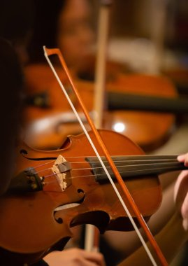 Closeup of the musician's hand is playing a violin in an orchestra.