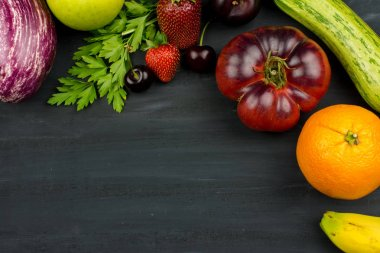 FRESH VEGTABLES AND FRUIT ON RUSTIC BLACK CHALK BACKGROUND. SPACE FOR TEXT. TOP VIEW.