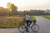 beautiful young woman with bicycle standing on road in evening