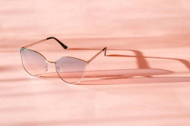 Metal frame sunglasses cast a shadow on the pink surface. Summer is coming concept.