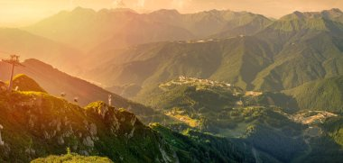 Panoramic view of the sunset in summer from the top of the Aibga range to the ski resort Rosa Khutor.
