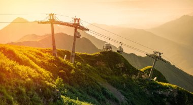 The cable car in the summer at the top of the Aibga ridge on the Rosa Khutor ski resort, illuminated by the bright orange sun at sunset. Krasnaya Polyana, Sochi, Russia.