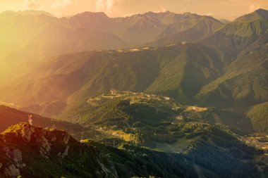 Summer view from the top of the Aibga range to the Rosa Khutor ski resort, illuminated by the bright orange sun at sunset. Krasnaya Polyana, Sochi, Russia.