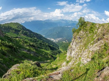 View from the top of the Aibga ridge to the ski resort, surrounded by high mountains. Krasnaya Polyana, Sochi, Caucasus, Russia.