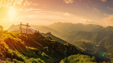 Panoramic view of the sunset in summer from the top of the Aibga range to the ski resort Rosa Khutor. Krasnaya Polyana, Sochi, Caucasus, Russia.