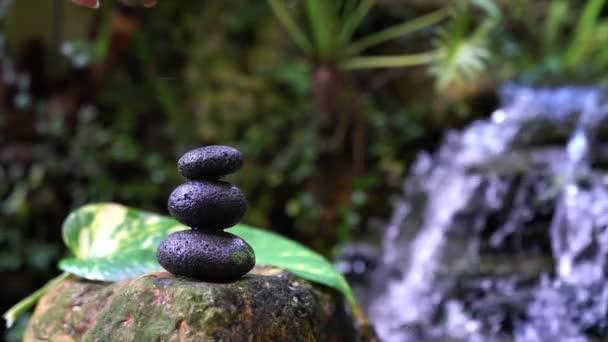 Žena položila kamenný oblázek na hromadu pyramidových kamenů s vodopádem a skalní zahradou v pozadí