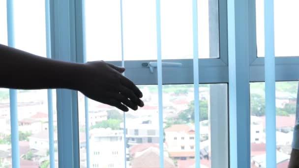 Dvě obchodnice různých etnik si potřesou rukou. Kancelářská okna se svislými žaluziemi jako pozadí.