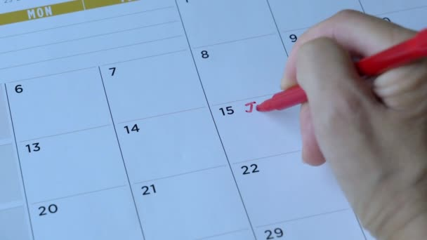 Woman writing down the words, job interview with red pen on calendar. Appointment reminder.