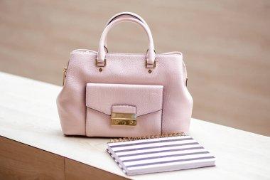 Close-up photo of modern light pink handbag near notebook planner