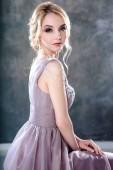 Menyasszony szőke nő egy modern színes esküvői ruha elegáns frizurával és töltsük fel. Divat szépség portréja textúrázott háttér