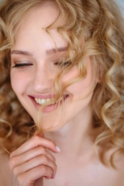 Close up portrait of blonde charming young woman with curly hair and natural makeup. Sunny morning, spa and care