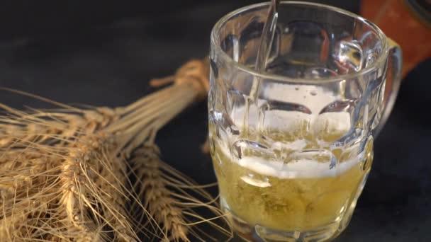 Bier ergießt sich in einen Becher. Bierbildende Wellen aus nächster Nähe. Das Einschenken von Bier in Becher mit Blasen aus nächster Nähe. Bier ergießt sich von oben in den Becher und bildet einen Schaum, der austritt. Zeitlupe