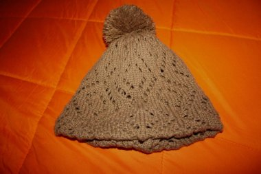 brown wool hat or cap, knitted. resting on a bright orange blanket or duvet.