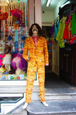 shop window display of clothes and party costumes. mannequin dressed as a famous character with rude colors. beard and long hair