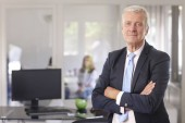 A senior financial advisor businessman standing with arms crossed at the office.