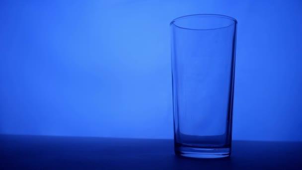 Prázdnou sklenici naplníte vodou. Modré světlo. Sklo čisté vody na červeném pozadí. Plnou sklenicí vody. Čistá voda se nalévá do sklenice. Plné Hd video.